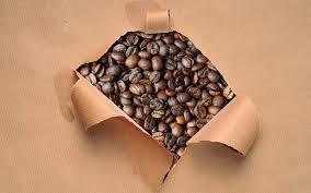 sobre rasgado en el que aparecen granos de café